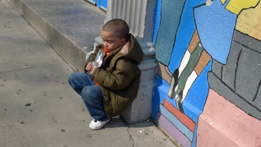Un chico bebiendo un batido a las puertas de su colegio, en Harlem.