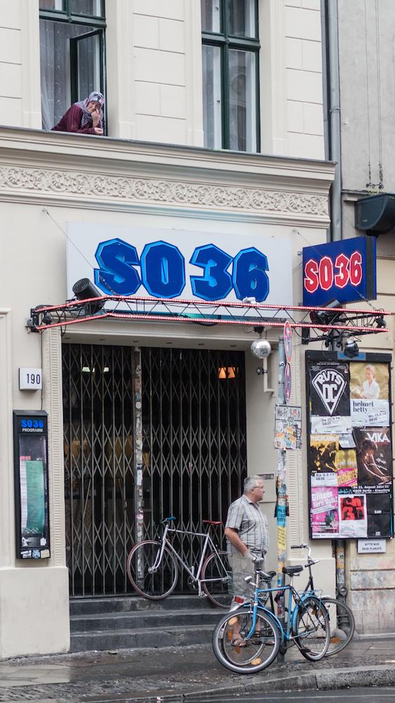 La fachada del SO36 a media tarde, con la señora asomada a su ventana y el señor esperando a alguien en la puerta, no previene de lo que habrá allí por la noche.